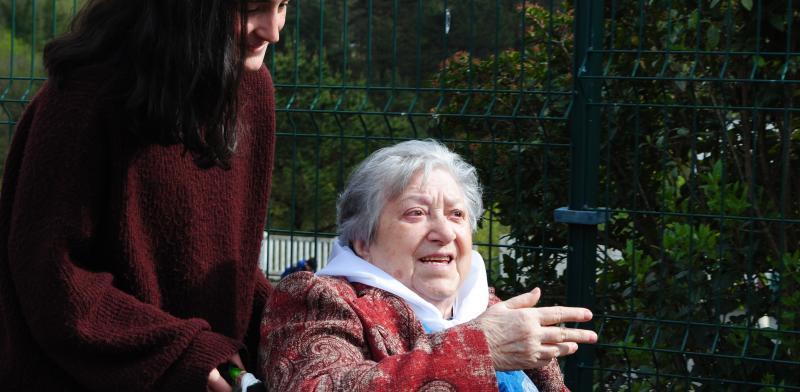 Estudiante empuje la silla de ruedas de una mujer mayor que le va hablando