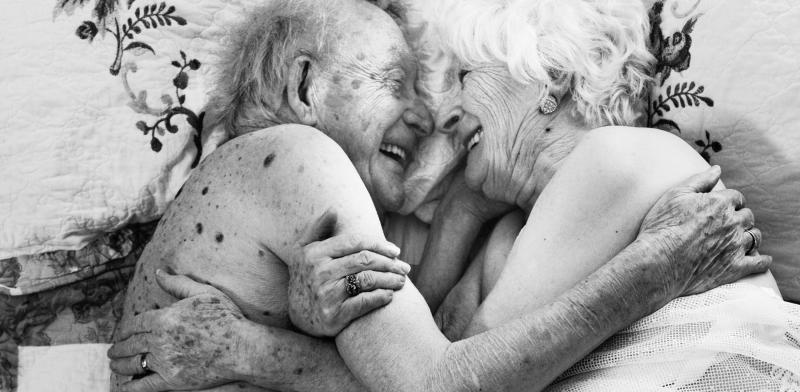 Un hombre y una mujer mayores se miran y sonríen tumbados en la cama