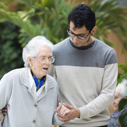 Mujer mayor paseando de la mano de su cuidador