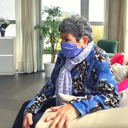 Mujer mayor sentada en un sofá con una mascarilla en el rostro